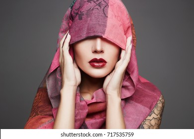 beautiful woman covers her face with a colored cloth.red lips girl.fashion islamic style woman in pink