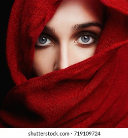 beautiful woman covers her face with a red cloth.fashion islamic style girl.make up