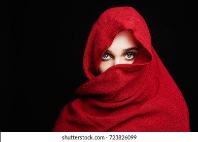 beautiful woman covers her face with a red cloth hi jab.fashion muslim style girl wrapped in a red hood