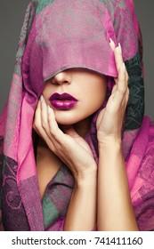 beautiful woman covers her face.purple lips make-up girl.fashion beauty portrait