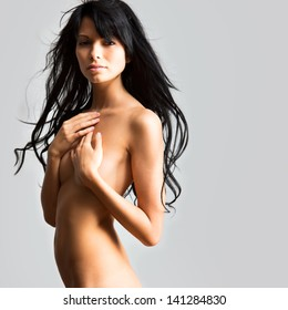 Beautiful woman covers her naked breasts with her hands