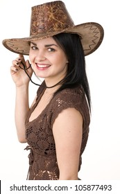 A beautiful woman in a cowboy hat. The natural portrait of a young attractive brunette on white background.