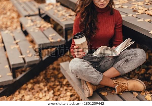 居心地の良い服を着た美人が本を読み、秋の公園の木のベンチに座ってコーヒーを飲む。
