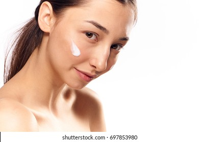 Beautiful woman with cream on face on isolated background portrait