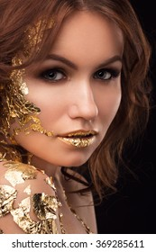 Beautiful woman with creative golden makeup and body art