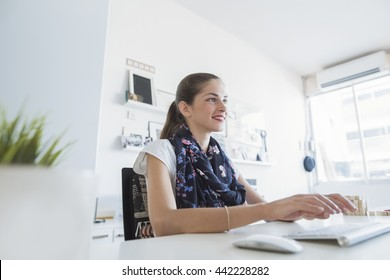 Beautiful woman creative professional is smiling, seating on her desk, typing on a keyboard, while in a modern working environment
