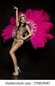 Beautiful woman in crown and carnival dress with feathers on black background