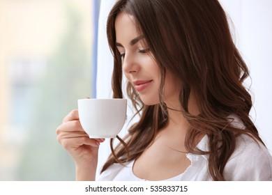 Beautiful woman with cup of aromatic coffee standing near window