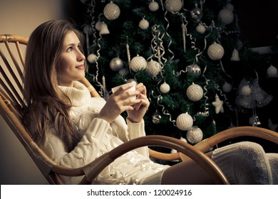 Beautiful woman with cup of coffee in chair. Christmas  decoration
