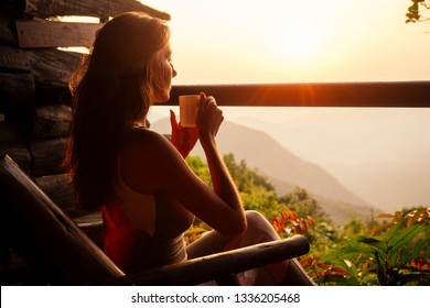 Beautiful woman with cup of coffee tea enjoying the view from the balcony on tea plantation jungle at India Kerala Goa wildernest nature spa resort