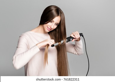 Beautiful woman curling long hair using curling iron.