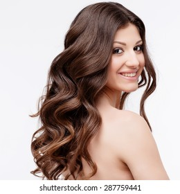 Beautiful Woman with curly brown hair close up. Youth Skin anf Hair Care Concept