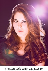 Beautiful woman with curly hair posing. Backlit and flare.