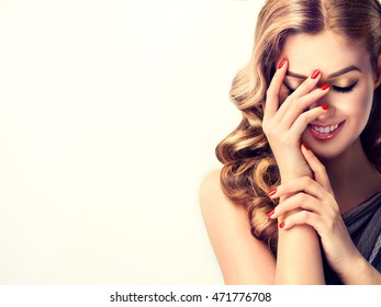 Beautiful woman with curly hair and red nails manicure . Girl laughs shyly closes her face with a hand .