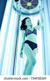 Beautiful woman or cute girl in swimsuit posing in solarium. Artificial  sunburn 9d88a62c1b