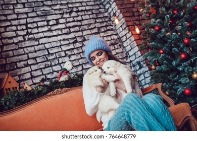 Beautiful woman with cute puppies sitting near Christmas tree. New Year.