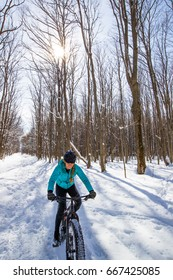 A beautiful woman cycling on a fat bike in the snow