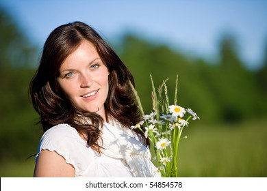 Beautiful woman with daisy flowers on sunny day