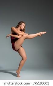 Beautiful woman dancer wearing maroon swimsuit posing on a grey studio background