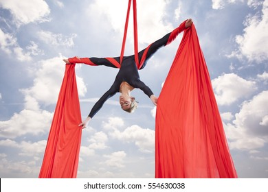 beautiful woman dancing with aerial silk on a sky background