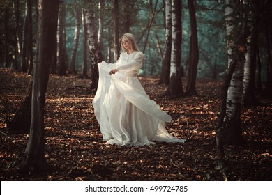 Beautiful woman dancing in autumn forest . Seasonal and colors