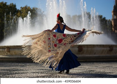 Beautiful woman dancing flamenco near the fountain