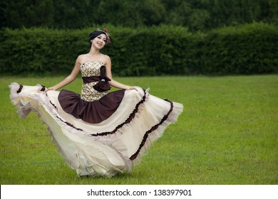 Beautiful woman dancing with formal dress at the park