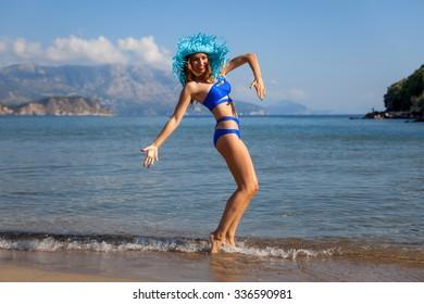 Beautiful woman dancing on a sand beach