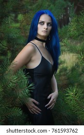 Beautiful woman with dark blue hair dressed in black dress in the magic forest. Gothic style.