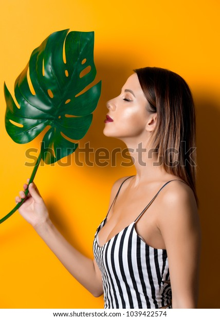 Beautiful woman in dark clothes with palm leaf on yellow color background