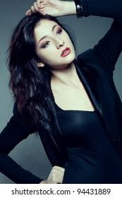 beautiful woman with dark hair holding hand on head