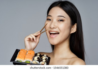 Beautiful woman with dark hair holds in her hand chopsticks sushi rolls set