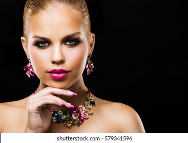 beautiful woman with dark makeup and pink lipstick posing on black background wearing flower spring and summer jewellry necklace