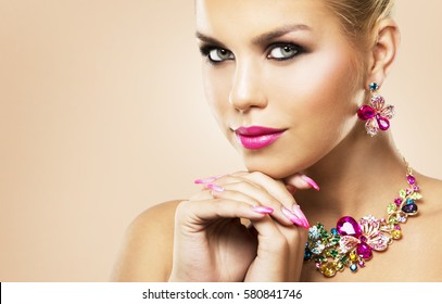 beautiful woman with dark makeup and pink lipstick posing on light beige background wearing flower spring and summer jewellry necklace