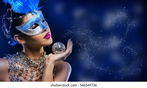beautiful woman with dark makeup and red lipstick posing on blue background. Wearing silver disco ball jewllery.