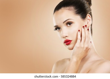 beautiful woman with dark makeup and red lipstick posing on light beige background