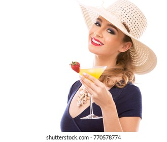 beautiful woman with dark makeup and red lipstick posing on white background wearing bright blue swimsuit and hat. Holding drink.