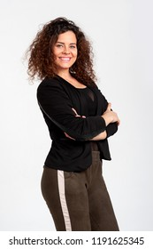 Beautiful woman with a dazzling open smile and a lush hairdo in Afro-style poses on a white background. The woman is dressed eclectically in khaki leggings and a shortened jacket.