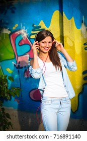Beautiful woman in denim and a white t-shirt listening to music on red headphones on graffiti background