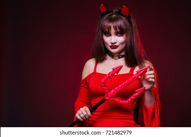 A beautiful woman in a devil costume with horns and pitchforks, a trident, in a red dress. American, dress for a costume party Halloween. Bright makeup