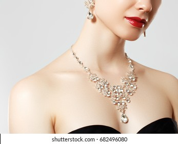 Beautiful woman with diamond necklace. Young beauty model with diamond pendant and earrings. Jewellery and accessories. Fashion and beauty salon. Perfect lip makeup
