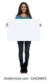 Beautiful woman displaying a blank whiteboard, full length on white.