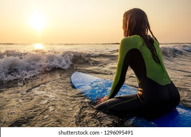 Beautiful woman in a diving suit for swimming surfing in the Indian Ocean on the background sunset sky and waves.professional surfer girl in a wetsuit doing sports at sea.extreme, adrenaline and youth
