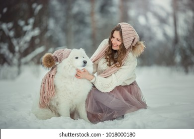 Beautiful woman with dog samoyed in winter forest
