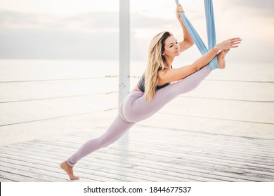 Beautiful woman doing antigravity yoga near by the sea at the morning.