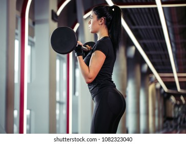 beautiful woman doing biceps curl with barbell in a gym