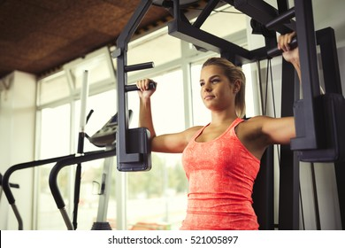 Beautiful woman doing chest exercises in gym