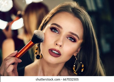 Beautiful woman doing evening makeup and holding makeup brush.