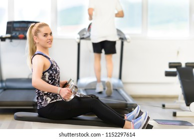 Beautiful woman doing exercises at at gym