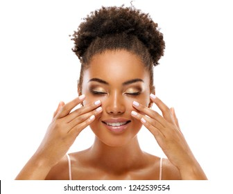 Beautiful woman doing facial massage, touching her face. Photo of african woman with clean healthy skin on white background. Skin care and beauty concept